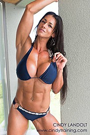 Cindy Landolt fitness model. Photoshoot of model Cindy Landolt demonstrating Body Modeling.Photoshoot of model Cindy Landolt demonstrating body modeling. Cindy wears a bejeweled blue bikini and earrings standing aside a wall in a front abs poseSwim