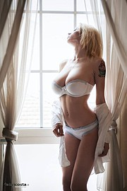 Natasha Legeyda model (modella). Photoshoot of model Natasha Legeyda demonstrating Body Modeling.Model Natasha in a modeling session wearing white lingerie, along a white shirt facing outwards the window. Photographed by Fabrizio CostaBody Modeling